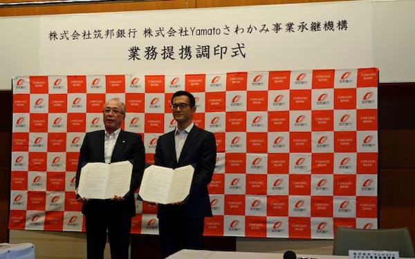 業務提携の調印式に出席した筑邦銀行の佐藤清一郎頭取(左)