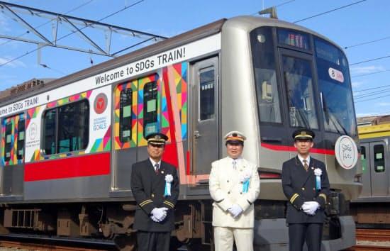 東急グループのSDGsトレインの前に立つ阪急・阪神・東急の各駅長ら
