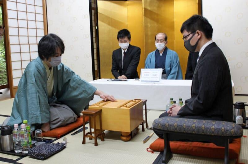 王座戦第2局で初手を指す久保九段(左、9日午前、京都市)