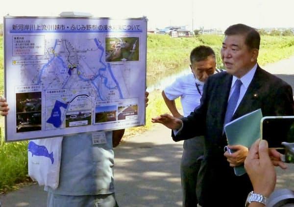 埼玉県ふじみ野市で水路を視察する自民党の石破元幹事長(9日午前)=共同