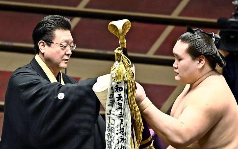 7月場所で師匠の伊勢ケ浜親方(左)から優勝旗を受け取る照ノ富士(日本相撲協会提供)=共同