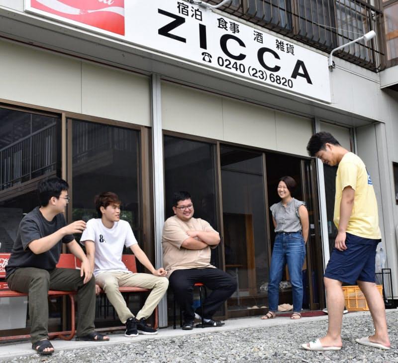 実家をもじった民泊「ZICCA」前でインターンの学生らと談笑する下枝浩徳さん(左から3人目、福島県葛尾村)