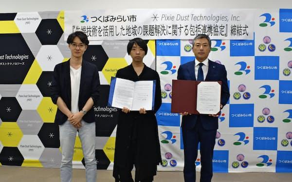 包括連携協定を結んだピクシーダストテクノロジーズの落合陽一CEO(中央)と小田川浩市長(右)(10日、茨城県つくばみらい市)