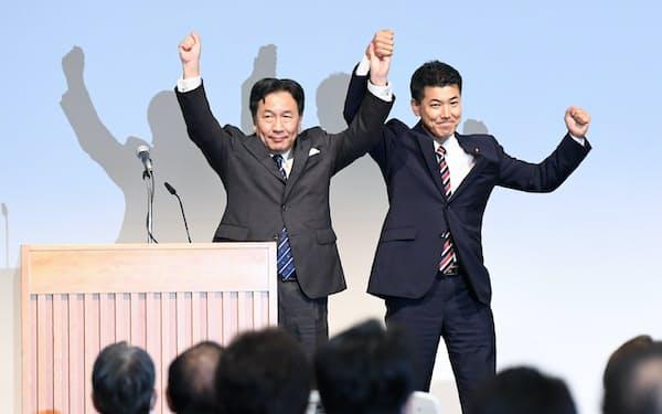 合流新党の代表に選出され、手を取り合う枝野幸男氏(左)と泉健太氏(10日、東京都千代田区)