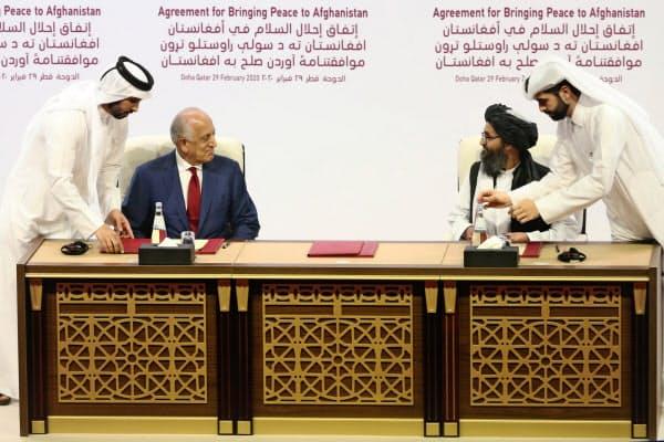 米特使(左)と平和協定に署名したアフガニスタンの反武装勢力タリバンの代表(2月29日、ドーハ)=AP