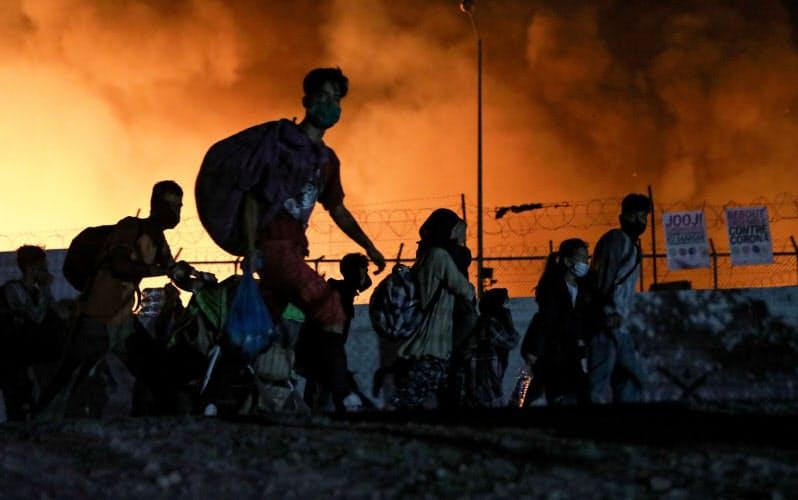 荷物を背負って避難するモリア難民キャンプの人々=ロイター