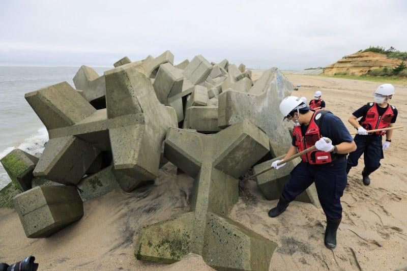 東日本大震災から9年半、行方不明者の手掛かりを求め宮城県山元町の海岸を捜索する県警亘理署員(11日午前)=共同