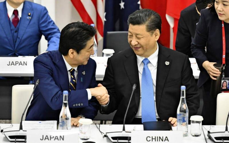 2019年6月、G20大阪サミットの会合で、中国の習近平国家主席(右)と笑顔で握手を交わす安倍首相=大阪市