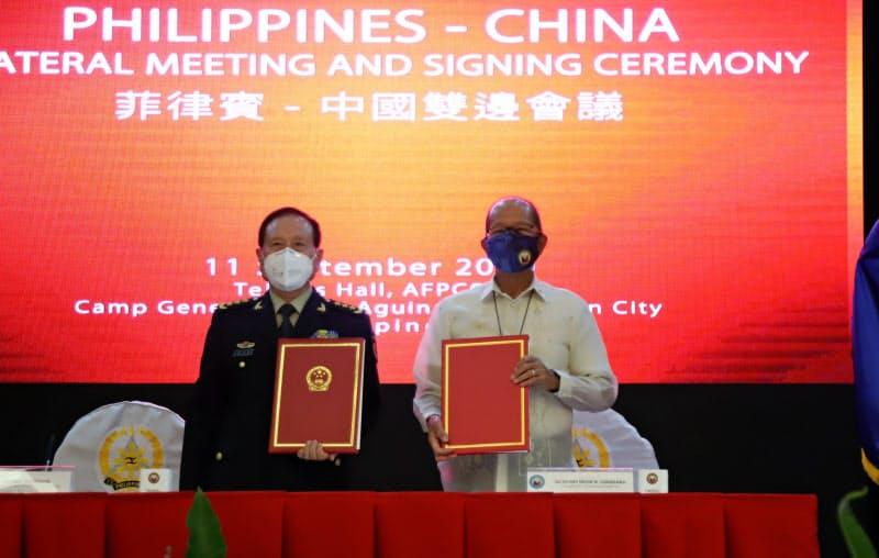 装備品提供で合意した中国の魏国防相(左)とフィリピンのロレンザーナ国防相(11日、マニラ)=比国防省提供