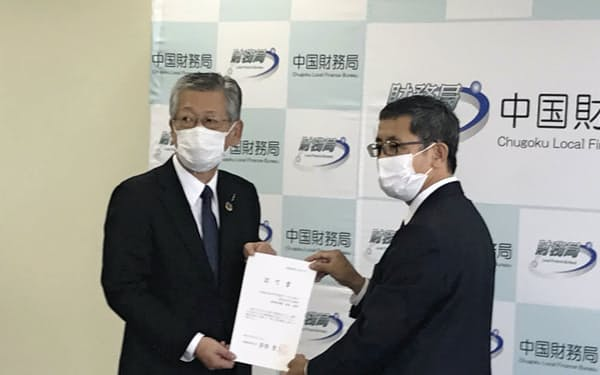 金森正樹中国財務局長(右)からひろぎんHDの設立認可書を受け取った広島銀の部谷頭取