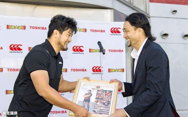 退団セレモニーで写真を贈られるラグビー元日本代表の大野均さん=右(11日、東京都府中市)=東芝提供・共同