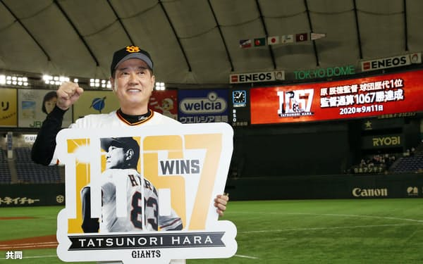 川上哲治元監督を抜いて球団歴代最多となる1067勝を挙げ、記念のボードを手にポーズをとる巨人・原監督(11日、東京ドーム)=共同