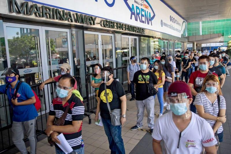フィリピンで新型コロナウイルスの検査のために並ぶ人々(8月、マニラ)=ロイター