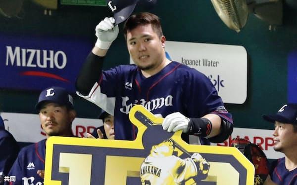 6回、通算150本塁打を放ち、記念ボードを手に観客に応える西武・山川(12日、ペイペイドーム)=共同