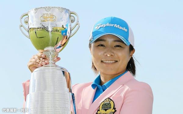 通算12アンダーで優勝し、カップを掲げ笑顔の永峰咲希(13日、JFE瀬戸内海GC)=代表撮影・共同