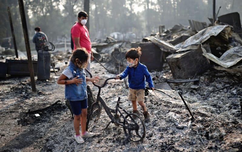 オレゴン州フェニックスの山火事に焼かれた自宅で自転車の残骸を見つけた子どもたち=ロイター