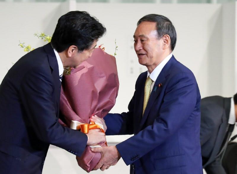自民党の新総裁となり、安倍首相にねぎらいの花束を手渡す菅氏(14日、東京都港区)