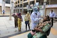 新型コロナウイルスの検査を受けるインドの人々(10日、グジャラート州)=AP