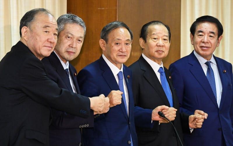 自民党臨時総務会で新四役と拳を合わせる菅総裁(中)(15日、党本部)