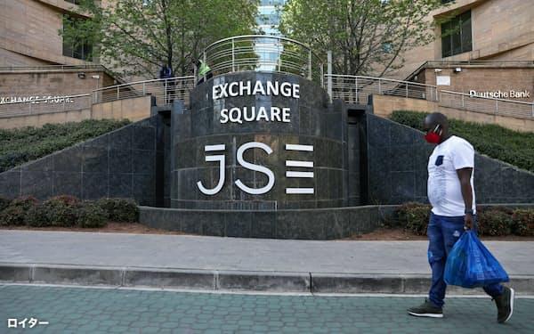 ヨハネスブルク証券取引所の前をマスク姿で歩く男性=ロイター