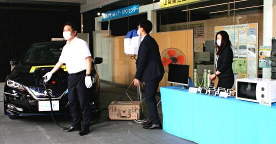 日産「リーフ」から家電などへの給電をデモする山梨県の長崎幸太郎知事(左)(15日、甲府市内)