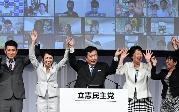 立憲民主党の結党大会で、両手を挙げる枝野代表(中)ら(15日、東京都港区)