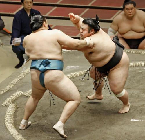 貴景勝(右)が押し出しで玉鷲を破る(16日、両国国技館)=共同