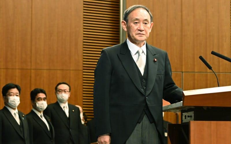 就任記者会見に臨む菅首相。左奥は加藤官房長官(16日、首相官邸)