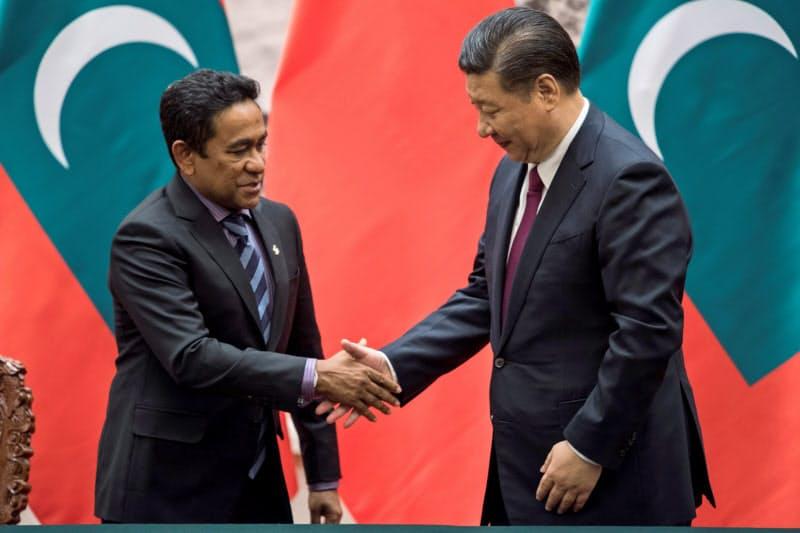 中国の習近平(シー・ジンピン)国家主席と握手する当時のヤミーン大統領(2017年12月、北京)=ロイター