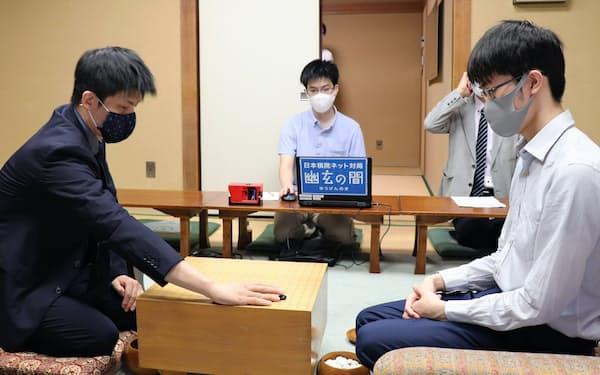 囲碁王座戦の挑戦者決定戦で初手を打つ張栩九段(左)。右は許家元八段(18日朝、東京都千代田区)