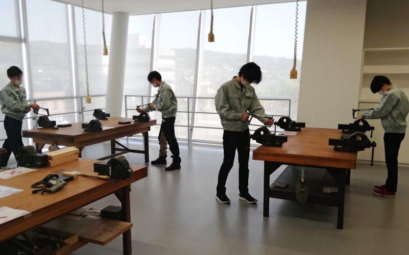 金沢工業大の「夢考房」で再開された講習会で、学生たちは感染防止のため互いに距離を空けて金属加工などを学んだ(石川県野々市市)