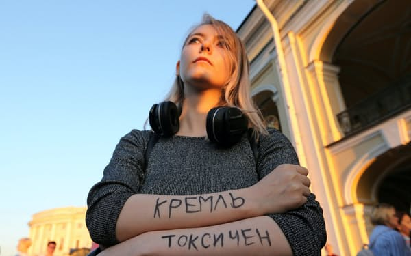 「クレムリン(ロシア大統領府)は有毒だ」と腕に書いて、ナワリヌイ氏の毒殺未遂疑惑に抗議するロシア市民(8月20日、サンクトペテルブルク)=ロイター