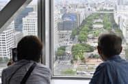 約1年8カ月ぶりに営業を再開した「名古屋テレビ塔」の展望台から街並みを眺める人たち=18日午前、名古屋市