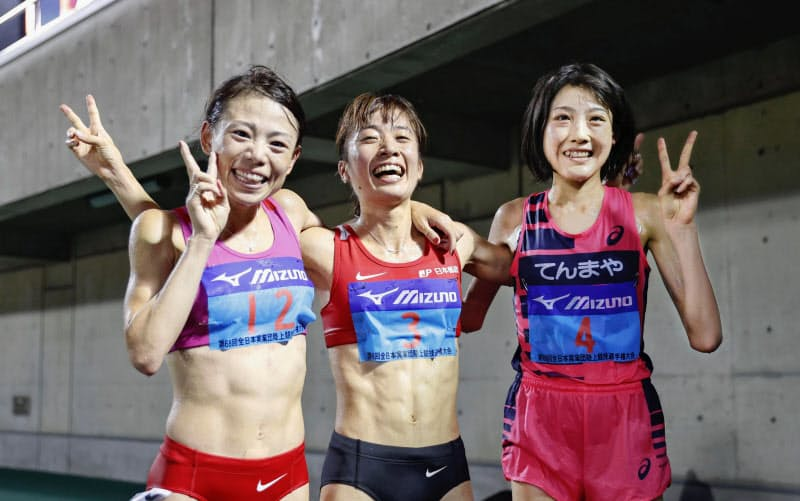 女子1万メートルで優勝し、2位の松田瑞生(左)、3位の前田穂南(右)と笑顔を見せる鍋島莉奈(18日、熊谷スポーツ文化公園陸上競技場)=共同