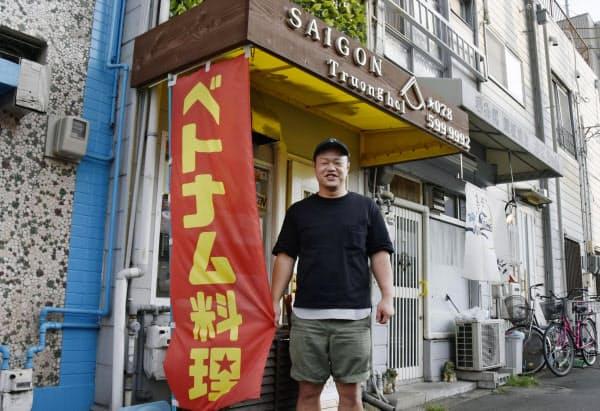 ベトナム料理店「サイゴンチュンハイ」の前に立つ石田長海さん(8月、神戸市)=共同