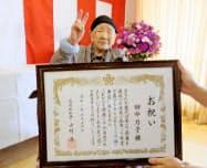 国内での歴代最高齢の記録を更新し、福岡県知事からホーム職員を通じて祝い状を受け取りポーズをとる田中カ子さん(19日午前、福岡市)=福岡県提供・共同