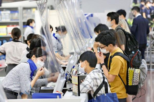 4連休の初日の19日、マスクを着用して羽田空港国内線のカウンターで手続きをする人たち=共同