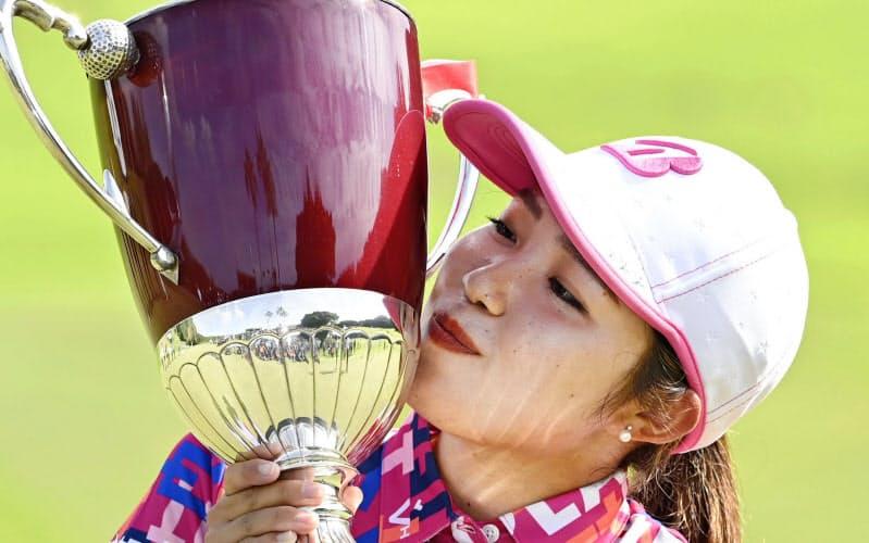 プレーオフを制してプロ転向後初優勝し、カップにキスをする古江彩佳(20日、新南愛知CC)=共同