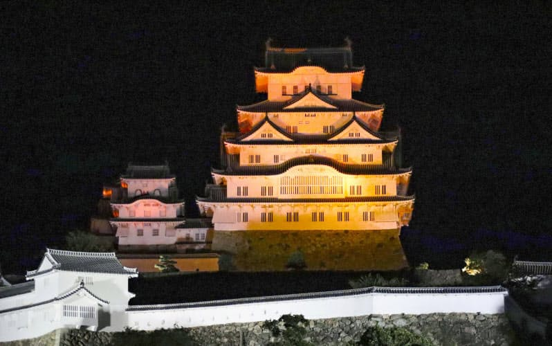 「世界アルツハイマーデー」に合わせ、オレンジ色にライトアップされた姫路城(21日夜、兵庫県姫路市)=共同
