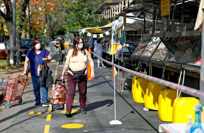 外出制限の中、マスクを着用し買い物に出かける市民(5月、ブエノスアイレス)=ロイター