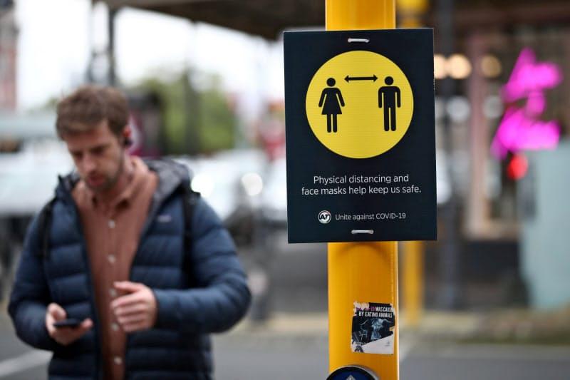 ニュージーランド北部のオークランドで、ソーシャルディスタンス(社会的距離)の維持を促す標識の近くを歩く男性(8月)=ロイター