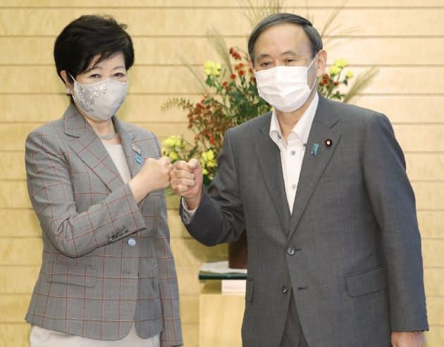 会談前のあいさつ代わりに拳を合わせる菅首相と小池東京都知事(左)(23日、首相官邸)