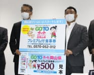 PRボードを掲げる両備HDの三宅副社長(左)とビザビの吉田社長(23日、岡山市)