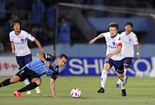 川崎戦に先発出場し、攻め込む横浜FCの三浦知良(右)。サッカーJ1最年長出場記録を大幅に更新した(23日、川崎市等々力陸上競技場)=共同