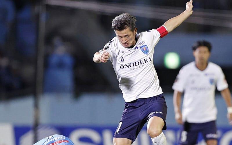 川崎戦に先発出場し、競り合う横浜FCの三浦知良(右)。サッカーJ1最年長出場記録を大幅に更新した=共同