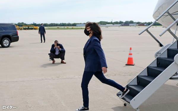 チャックテイラーを履いて飛行機から降りるハリス氏=ロイター