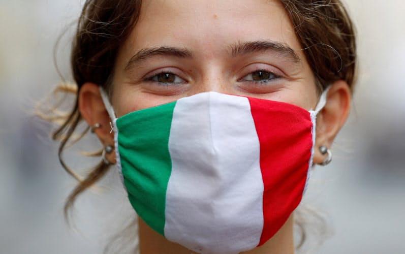 ローマでイタリア国旗の色のマスクを付ける女性。専門家は、マスクの強制着用がイタリアの新型コロナ対策成功の理由のひとつとみる=ロイター