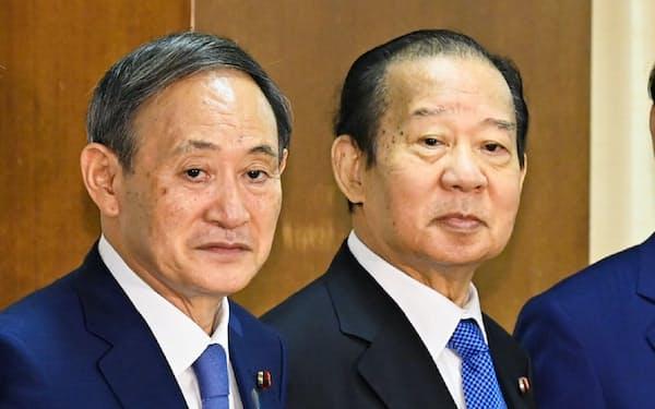 自民党臨時総務会で拳を合わせる菅新総裁と二階幹事長
