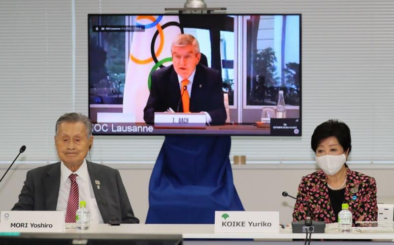 リモート参加であいさつするIOCのバッハ会長(奥)と出席した(左から)東京五輪・パラリンピック組織委の森会長と小池都知事(24日、東京都中央区)