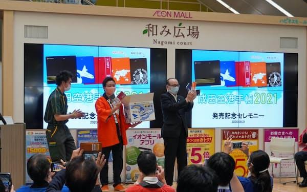 発売イベントで小泉一成・成田市長(中央)も手帳をPR(21日、イオンモール成田)